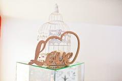 Amor de madeira da letra no cubo do espelho e na gaiola branca da decoração no weddin Imagem de Stock Royalty Free