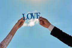 Amor de madera azul de la palabra en las manos de los pares de la boda en un cielo azul Imagen de archivo libre de regalías