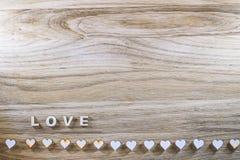 Amor de madera de la palabra y el corazón en un fondo rústico Día de tarjeta del día de San Valentín Imágenes de archivo libres de regalías