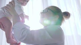 Amor de madre, niño del dodnimaet de la mamá en manos para arriba en sitio cerca de la ventana en el fondo de cortinas metrajes