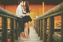 Amor descalzo - besos de los pares ardientemente en el puente de madera imagenes de archivo