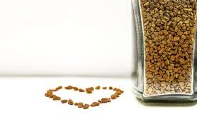 Amor do café - grânulo do café instantâneo na garrafa e no sinal do coração imagem de stock royalty free