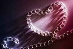 amor do conceito e relacionamentos humanos Forma do coração feita da corrente do ferro inclinações azuis e vermelhos no fundo Dia imagens de stock royalty free