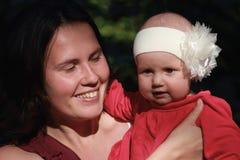Amor dos pais O bebê bonito que senta-se no ` s da mamã arma-se Y feliz Imagem de Stock