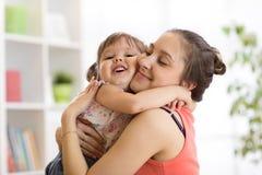 Amor e conceito dos povos da família - filha feliz da mãe e da criança que abraça em casa foto de stock royalty free