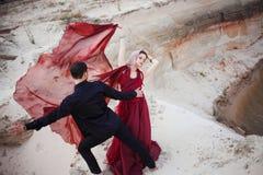 Amor e paixão, conceito Dança nova bonita dos pares no deserto O homem no preto e mulher no vermelho imagem de stock