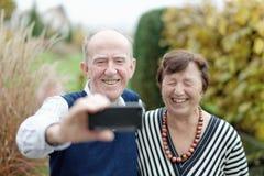Amor en foco Pares mayores felices que enlazan el uno al otro y que hacen el selfie Foto de archivo