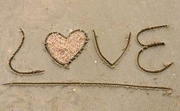 AMOR escrito en la playa arenosa Fotos de archivo libres de regalías