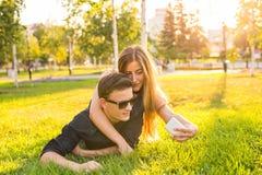 Amor, gente y concepto de la tecnología - par adolescente feliz que miente en hierba y que toma el selfie en smartphone en el ver Fotos de archivo libres de regalías