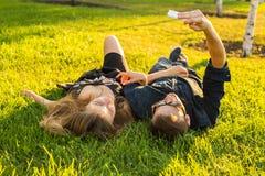 Amor, gente y concepto de la tecnología - par adolescente feliz que miente en hierba y que toma el selfie en smartphone en el ver Fotografía de archivo