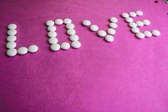 Amor hermoso de la inscripción hecho de píldoras de la ronda blanca, de vitaminas, de los antibióticos y del espacio médicos liso imágenes de archivo libres de regalías