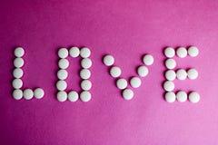 Amor hermoso de la inscripción hecho de píldoras de la ronda blanca, de vitaminas, de los antibióticos y del espacio médicos liso imagen de archivo libre de regalías