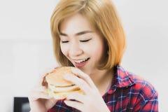 Amor hermoso encantador de la mujer que come la hamburguesa La hamburguesa tiene tr imagenes de archivo