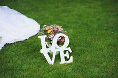 Amor - inscripción de madera para casarse en hierba verde Fotos de archivo libres de regalías