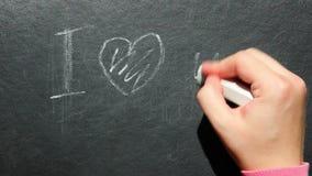 Amor - la mano de la mujer escribe el texto con tiza en la pizarra