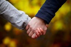 Amor - mãos da terra arrendada dos pares no outono Imagem de Stock
