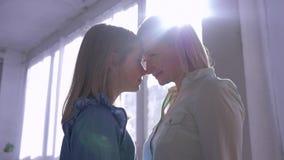Amor materno, mãe feliz com a filha a aconchegar-se um com o otro acima das cabeças em retroiluminado contra a janela