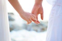 Amor - par romántico que lleva a cabo las manos en una playa en puesta del sol Foto de archivo libre de regalías