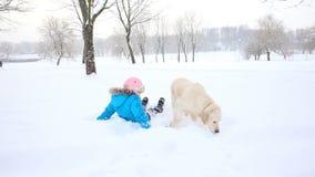 Amor para los animales domésticos - la muchacha está descansando con un golden retriever en la nieve en el parque metrajes