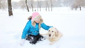 Amor para los animales domésticos - la muchacha está descansando con un golden retriever en la nieve en el parque almacen de video