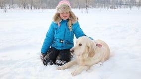 Amor para los animales domésticos - la muchacha está descansando con un golden retriever en la nieve en el parque almacen de metraje de vídeo