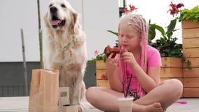 Amor para los animales domésticos - la muchacha hermosa de la moda con las coletas africanas come en la calle con su perro almacen de video