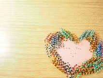 Amor que você etiqueta na nota pegajosa com colocar clipes de papel Fotografia de Stock Royalty Free