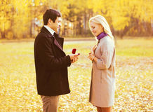 Amor, relacionamentos, conceito do acoplamento e do casamento - o homem propõe uma mulher casar-se, anel vermelho da caixa, par r fotografia de stock royalty free