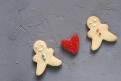 Amor rojo del corazón entre dos personas en un fondo gris Concepto del día de tarjetas del día de San Valentín Imagen de archivo libre de regalías