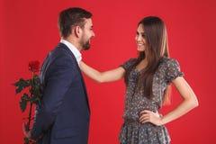 Amor, romance, dia de Valentim, pares e conceito dos povos - homem novo feliz que dá a flor vermelha à mulher de sorriso imagens de stock royalty free