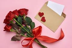 Amor verdadeiro Envelope com nota de papel, ramalhete das rosas com fita vermelha fotografia de stock