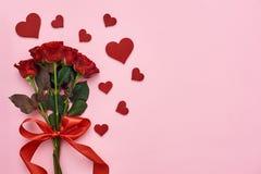 Amor verdadeiro Ramalhete das rosas com a fita vermelha para ela com corações de papel decorativos fotografia de stock