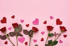 Amor verdadeiro Rosas vermelhas com corações de papel decorativos no fundo cor-de-rosa imagem de stock royalty free