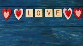 amor vermelho da rotulação dos corações bonitos, em um fundo de madeira azul Imagens de Stock Royalty Free