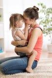 Amor y concepto de la gente de la familia - hija feliz de la madre y del niño que abraza en casa fotografía de archivo