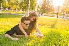 Amor y concepto de la gente - par adolescente feliz que miente en hierba y que toma el selfie en smartphone en el verano Fotos de archivo libres de regalías