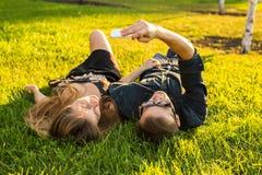 Amor y concepto de la gente - par adolescente feliz que miente en hierba y que toma el selfie en smartphone en el verano Foto de archivo libre de regalías