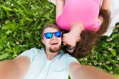 Amor y concepto de la gente - par caucásico adolescente feliz en las gafas de sol que mienten en hierba y que toman el selfie en  Imagen de archivo libre de regalías