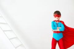 amorce Le superhéros de garçon dans un manteau rouge Images stock