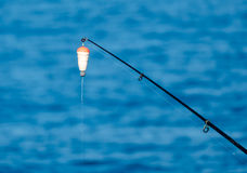 Amorce-tige de pêche avec le flotteur contre la surface bleue d'eau de mer Photo libre de droits