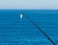 Amorce-tige de pêche avec le flotteur contre la surface bleue d'eau de mer Photographie stock libre de droits