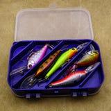 Amorces pour pêcher sur le fond de toile Plusieurs wobblers de différentes couleurs dans la boîte pour des attirails de pêche Photo stock