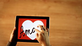 Amore calligraphy. Female writing inside white heart on tablet stock video