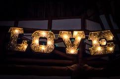 Amore dell'iscrizione dalla lampadina elettrica sulla lavagna di legno Fotografie Stock Libere da Diritti
