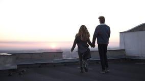 Amore della gioventù Belle coppie divertendosi tempo insieme sull'alto tetto di costruzione Correre, ballando ed abbracciare gorg video d archivio