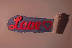 Amore di parola in carta lacerata fotografia stock