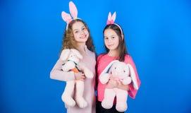 Amore di speranza e vita allegra Bambini con i giocattoli del coniglietto su fondo blu Sorelle costumi svegli sorridenti del coni immagine stock libera da diritti