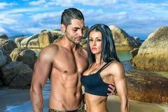 Amore e muscoli sulla spiaggia dei massi Fotografia Stock