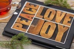 Amore, gioia e pace sulla compressa digitale fotografia stock libera da diritti