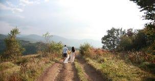 Amore nelle montagne L'uomo e il woiman funzionano lungo la strada all'orizzonte da qualche parte sulla collina mentre il sole sp archivi video